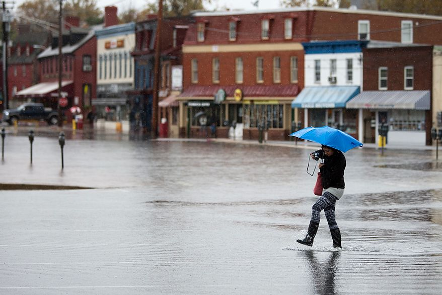 Noreen B., 15, from Annapolis, Md., walks through flooded Dock St. in downtown Annapolis, Md., Tuesday, Oct. 30, 2012. The storm left early a foot and half of water but the stores are more worried about the tide which rises at 5:45pm and could bring another two feet of water. (Craig Bisacre/The Washington Times)