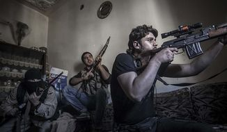 In this Monday, Oct. 29, 2012, photo, a rebel sniper aims at Syrian army positions in the Aleppo Jedida district, Syria. (AP Photo/Narciso Contreras).
