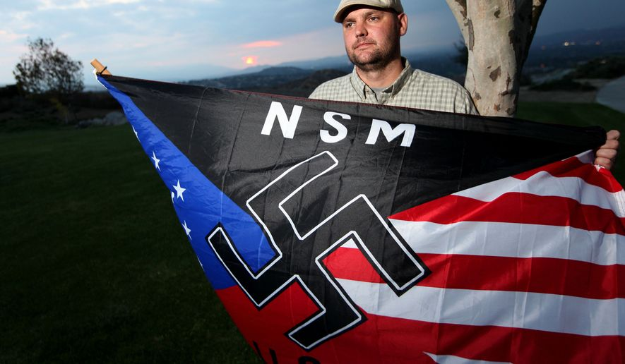 Jeff Hall holds a neo-Nazi flag while standing at Sycamore Highlands Park near his home in Riverside, Calif., in October 2010. (AP Photo/Sandy Huffaker)