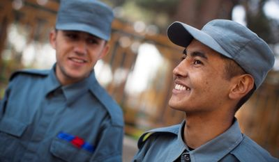 """Azim Aga, right, from northern Baghlan province, a fresh police recruit, smiles during a break at the police academy in Kabul, Afghanistan. """"Right now the police who are on the street are not educated and are from the jihad, a reference to Afghanistan's successive wars, 'We will be proud policemen.'"""" Aga said. (AP Photo/Anja Niedringhaus)"""