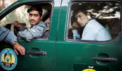 A new recruit of the Afghan National Police force, right, is driven to his new outpost straight from the registration center in Kabul, Afghanistan.  (AP Photo/Anja Niedringhaus)