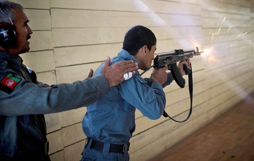 An Afghan instructor instructs a police student shooting with live ammunition at the police academy in Kabul, Afghanistan.  (AP Photo/Anja Niedringhaus)