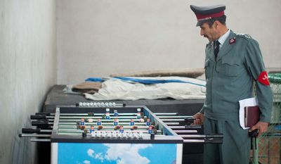 """Afghan National Police Academy Director Maula Dad Pazoish tries out a table football in a recreation room at the police academy in Kabul, Afghanistan. """"The people brought into the police are bringing a bad name to the police, not just in Kabul but all over in the provinces. They are bringing us a bad reputation because of lack of education"""", Maula said. (AP Photo/Anja Niedringhaus)"""