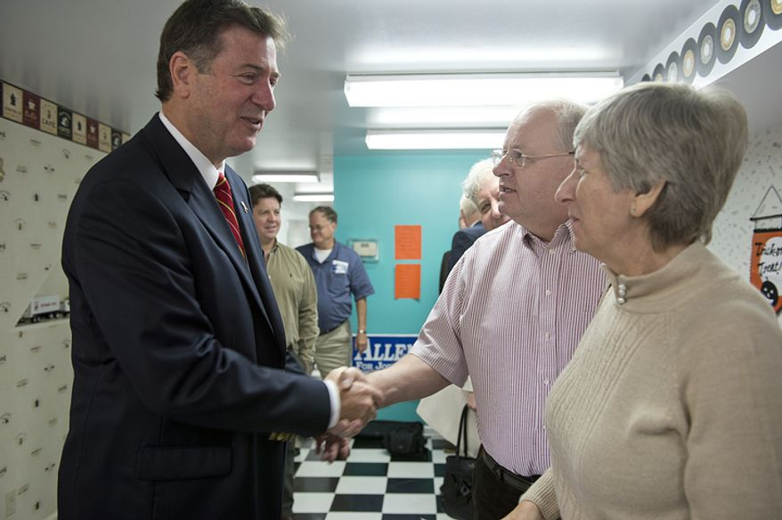 Former Virginia Gov. George Allen, who is running for U.S. Senate, shakes hands with Steve Riley of West Springfield, Va., while talking with him and his wife Kathy following a town hall meeting at Joe Ragan's Coffee House in Springfield, Va., on Wednesday, Oct. 31, 2012. Allen talked with attendees about their concerns, including health care and creating jobs. (Barbara L. Salisbury/The Washington Times)
