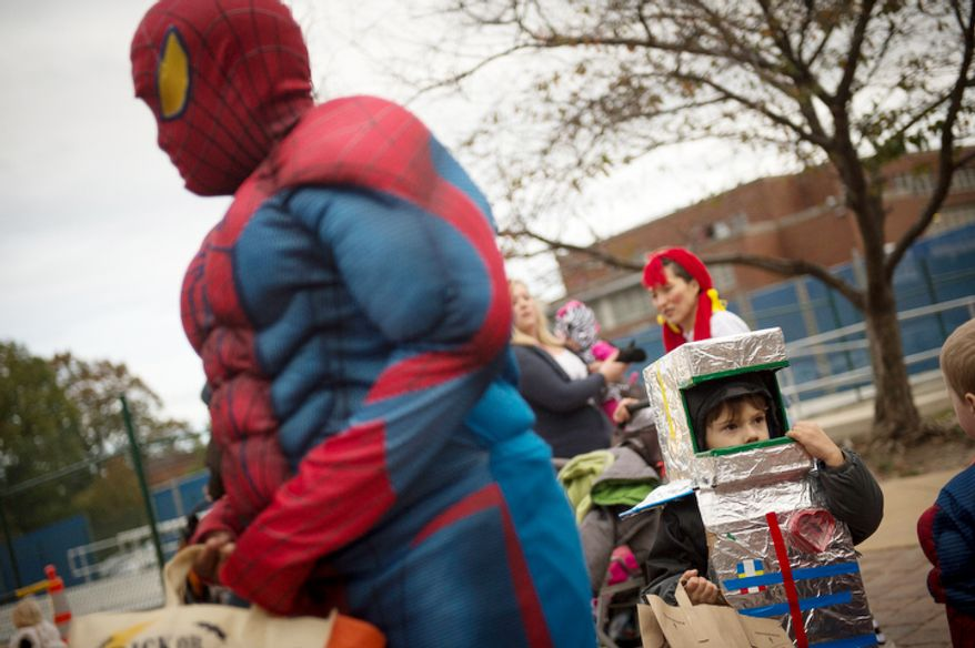 Micah Taylor,4, (right) and John Gardner,12, (left) both of Washington, D.C., join other residents for Halloween festivities at Eastern Market in Washington, D.C., Wednesday, Oct. 31, 2012. (Rod Lamkey Jr./The Washington Times)