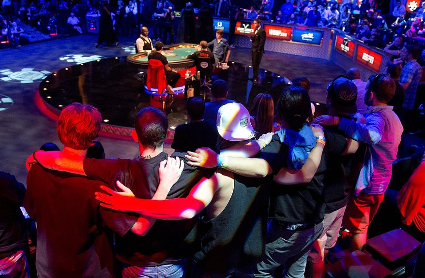 Supporters of Jesse Sylvia lock arms as they watch play in the 348th hand during the World Series of Poker Final Table event, Wednesday, Oct. 31, 2012, in Las Vegas. Sylvia won the hand and a four-bet pot. (AP Photo/Julie Jacobson)