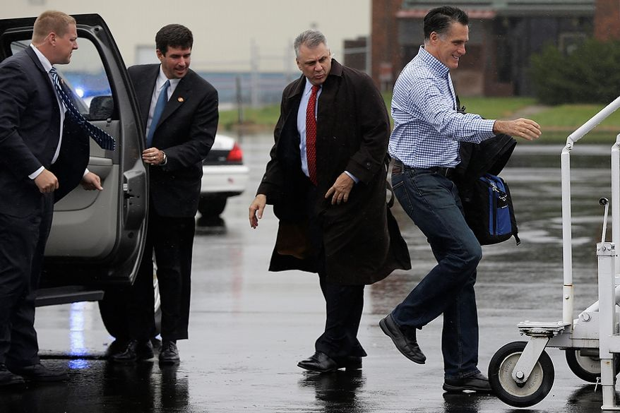 U.S. Secret Service agents watch as Republican presidential candidate, former Massachusetts Gov. Mitt Romney walks in a drizzle to board his campaign plane in Vandalia, Ohio, Tuesday, Oct. 30, 2012, as he travels to Tampa, Fla. for a campaign stop. (AP Photo/Charles Dharapak)