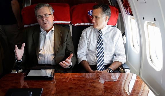 Republican presidential candidate, former Massachusetts Gov. Mitt Romney talks with former Florida Gov. Jeb Bush as they fly on his campaign plane to Miami Fla., Wednesday, Oct. 31, 2012. (AP Photo/Charles Dharapak)