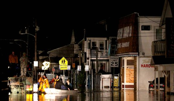 Rescue workers help stranded people out of their flooded homes in Seaside Heights, N.J., following the arrival of superstorm Sandy, Tuesday, Oct. 30, 2012. Sandy, the storm that made landfall Monday, caused multiple fatalities, halted mass transit and cut power to more than 6 million homes and businesses. (AP Photo/Julio Cortez)