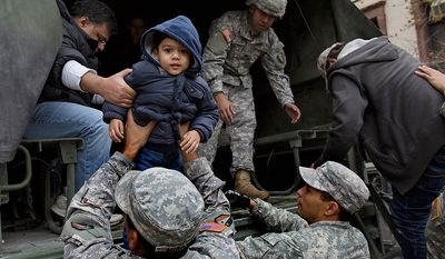 Vihaan Gadodia, 2, is handed from a National Guard truck after he and his family left a flooded building in Hoboken, N.J., Wednesday, Oct. 31, 2012, in the wake of superstorm Sandy. Some residents are being plucked from their homes by large trucks as parts of the city are still covered in standing water. (AP Photo/Craig Ruttle)