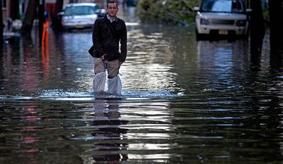 David Bagatelle, of Hoboken, N.J., walks from his residence on Park Avenue through high water in Hoboken, N.J., Wednesday, Oct. 31, 2012, in the wake of superstorm Sandy. Bagatelle's home is surrounded by water, but dry, where his wife and 7day-old baby are staying. (AP Photo/Craig Ruttle)