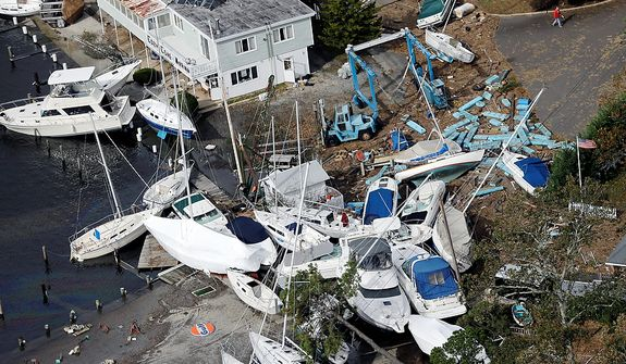In this aerial photo, upended boats are piled together at a marina along the central New Jersey shore on Wednesday, Oct. 31, 2012. New Jersey got the brunt of superstorm Sandy, which made landfall in the state and killed six people. More than 2 million customers were without power as of Wednesday afternoon, down from a peak of 2.7 million. (AP Photo/Mike Groll)