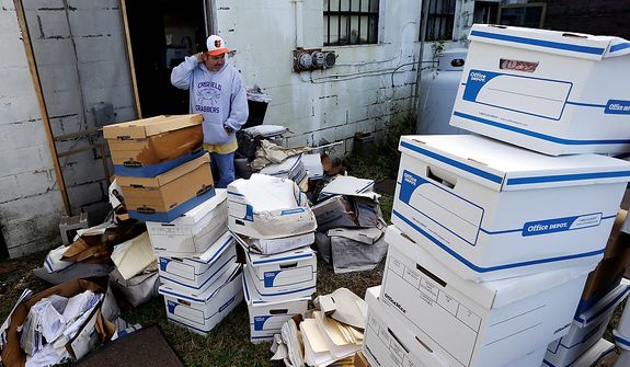 Certified Public Accountant John Sterling looks at damaged boxes of records removed from his office after superstorm Sandy, Wednesday, Oct. 31, 2012, in Crisfield, Md. Most of the records were old and on their way to the shredder he said. (AP Photo/Alex Brandon)