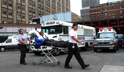 A patient is taken to a waiting medical transport vehicle outside Bellevue Hospital in New York Wednesday Oct. 31, 2012. Mayor Michael Bloomberg says Bellevue Hospital is evacuating 500 patients due to storm damage. Bloomberg said Wednesday that officials are in the process of finding beds for the patients. Workers have been pumping about 17 million gallons of water out of the basement. (AP Photo/Tina Fineberg)