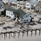 People survey the destruction left in the wake of Superstorm Sandy on Wednesday, Oct. 31, 2012, in Seaside Heights, N.J. (AP Photo/Mike Groll)