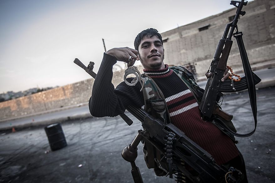 In this Sunday, Oct. 28, 2012, photo, a rebel fighter poses holding handcuffs in the front-line neighborhood of Bustan Al-Pasha shortly after an army jet hits the rebel position in northeast Aleppo, Syria. Syria's air force fired missiles and dropped barrel bombs on rebel strongholds while opposition fighters attacked regime positions, flouting a U.N.-backed cease-fire that was supposed to quiet fighting over a long holiday weekend but never took hold. (AP Photo/Narciso Contreras)