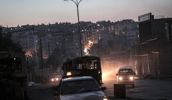 In this Tuesday, Oct. 30, 2012, photo, night falls on a Syrian rebel checkpoint in the Bustan Al-Pasha neighborhood, the boundary of the area controlled by rebel fighters at the northeast limit of the Kurdish-controlled area of Sheikh Maksoud in Aleppo, Syria. (AP Photo/Narciso Contreras)