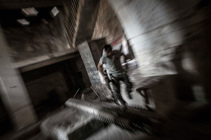 In this Monday, Oct. 29, 2012, photo, a rebel fighter belonging to the Qatebee Sokor Al-Islam group sneaks through a residential building as he looks for a firing position during clashes between rebel fighters and the Syrian army in the Jedida district of Aleppo, Syria. Syrian fighter jets pounded rebel areas across the country on Monday with scores of airstrikes that anti-regime activists called the most widespread bombing in a single day since Syria's troubles started 19 months ago.(AP Photo/Narciso Contreras)