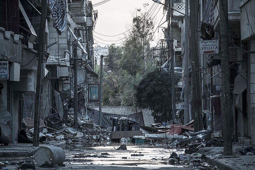 In this Tuesday, Oct. 30, 2012, photo, destroyed buildings are seen along a desolated street in the Bustan Al-Pasha district after several weeks of intense battles between rebel fighters and the Syrian army in Aleppo, Syria. (AP Photo/Narciso Contreras)