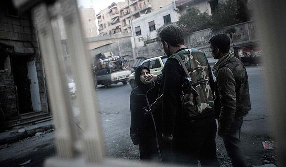 In this Tuesday, Oct. 30, 2012, photo, a Syrian woman is stopped and questioned by rebels at a checkpoint in the Bustan Al-Pasha neighborhood, the boundary of the rebel-controlled area at the northeast limit of the Sheikh Maaksoud neighborhood in Aleppo, Syria. (AP Photo/Narciso Contreras)