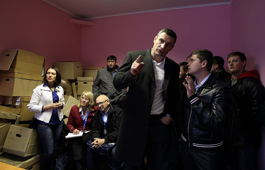 Vitali Klitschko (center), chairman of the Ukrainian opposition party Udar (Punch) and WBC heavyweight champion boxer, speaks with members of the election commission at their office in Brovary, Ukraine, on Tuesday, Oct. 30, 2012. Ukrainian opposition parties are scrambling for position after the ruling party scored a confident victory in parliamentary elections denounced as unfair by international observers. (AP Photo/Olexander Kosarev)