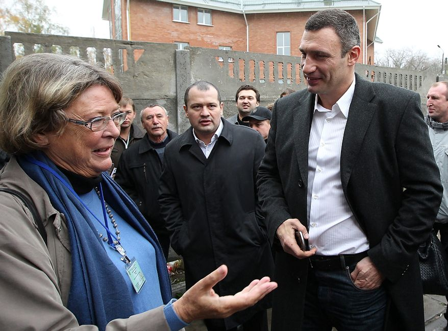 Vitali Klitschko (right), chairman of the Ukrainian opposition party Udar (Punch) and WBC heavyweight champion boxer, speaks with  international election observer Hanne Severinsen in Brovary, Ukraine, on Tuesday, Oct. 30, 2012. Ukrainian opposition parties are scrambling for position after the ruling party scored a confident victory in parliamentary elections denounced as unfair by international observers. (AP Photo/Olexander Kosarev)