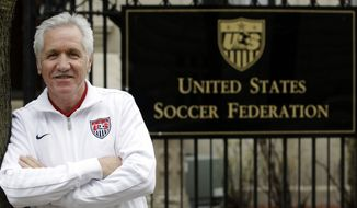 In this Tuesday, Oct. 30, 2012, photo, Tom Sermanni, new coach of the United States women's soccer team, poses for a photo outside the United States Soccer Federation Headquarters after an interview with The Associated Press in Chicago. Sermanni was hired Tuesday to replace Pia Sundhage, who led the Americans to back-to-back Olympic gold medals and their first World Cup final in 12 years. Sermanni has spent the last eight years as Australia's coach, taking the Matildas to the quarterfinals of the last two Women's World Cups. (AP Photo/M. Spencer Green)