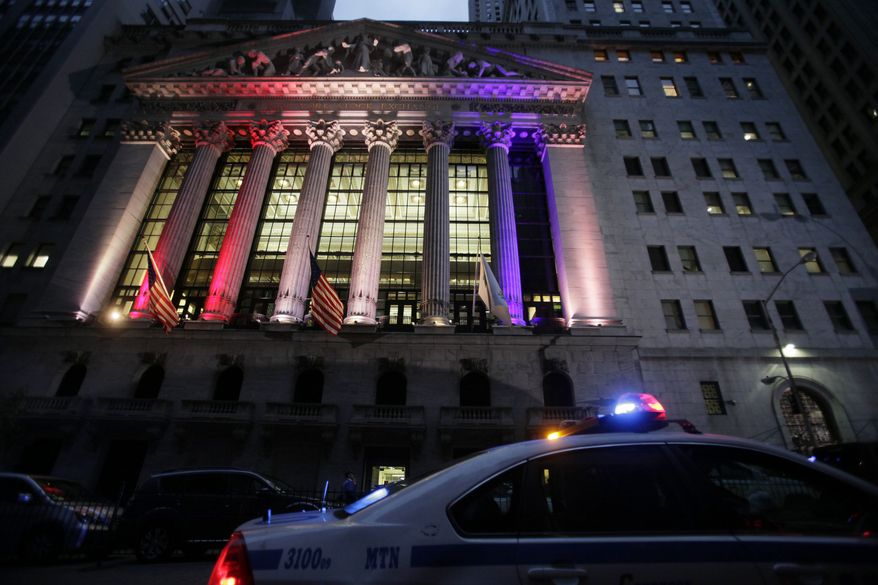 A police car patrols in front of the New York Stock Exchange, Wednesday, Oct. 31, 2012, before it reopens for trading for the first time this week following a two-day shutdown due to superstorm Sandy. Stock futures are rising ahead of the opening bell. (AP Photo/Mark Lennihan)