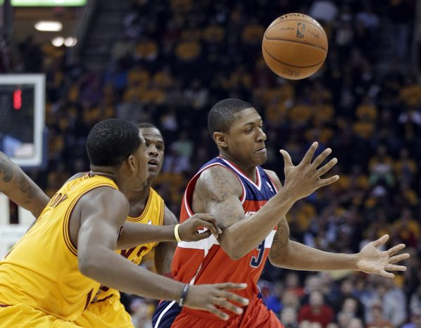 Washington Wizards' Bradley Beal, right, loses control of the ball under pressure from the Cleveland Cavaliers in the first quarter of an NBA basketball game Tuesday, Oct. 30, 2012, in Cleveland. (AP Photo/Mark Duncan)