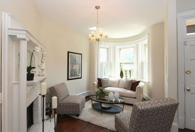 At the front of the home at 718 East Capitol St. NE is a bay-window alcove with tall windows. The alcove faces a wood-burning fireplace that features a detailed white-painted mantel.