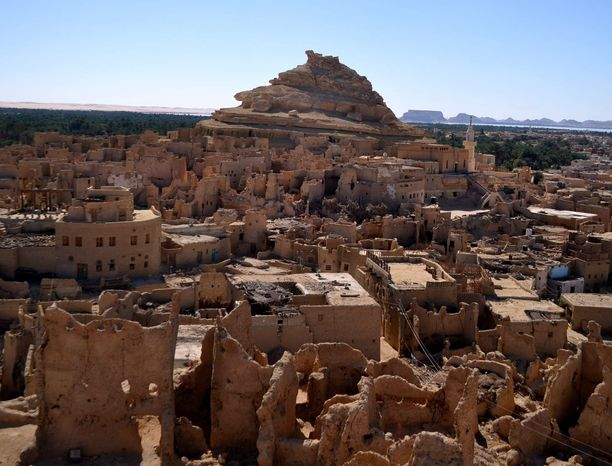 The Roman-era necropolis known as the Mountain of the Dead looms in the background in Siwa, Egypt. The town is known for its ancient ruins, natural springs and rolling sand dunes. (Associated Press)