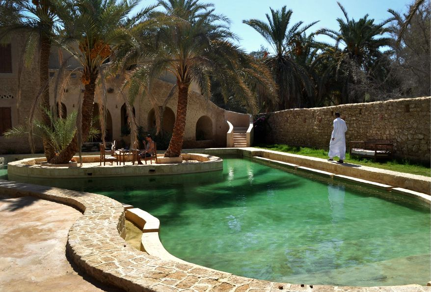 People relax by a freshwater pool at the Ghaliet Ecolodge and Spa in the Egyptian oasis of Siwa, a Berber town of some 27,000 people roughly 450 miles southwest of Cairo. The palm tree-lined area is known for its quiet charm, ancient ruins, abundant natural springs and rolling sand dunes in the surrounding desert. (AP Photo/Kim Gamel)