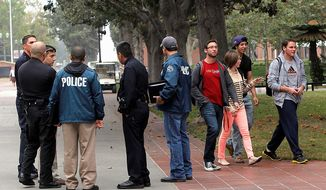 University students walk to classes as Los Angeles police officers investigate a shooting that occurred Wed. night at a halloween party on the University of Southern California Campus in Los Angeles on Thursday, Nov. 1, 2012. Los Angeles police say two men apprehended after a Halloween shooting on the USC campus are still being interviewed and three of the four people wounded have been released from the hospital. (AP Photo/Nick Ut)