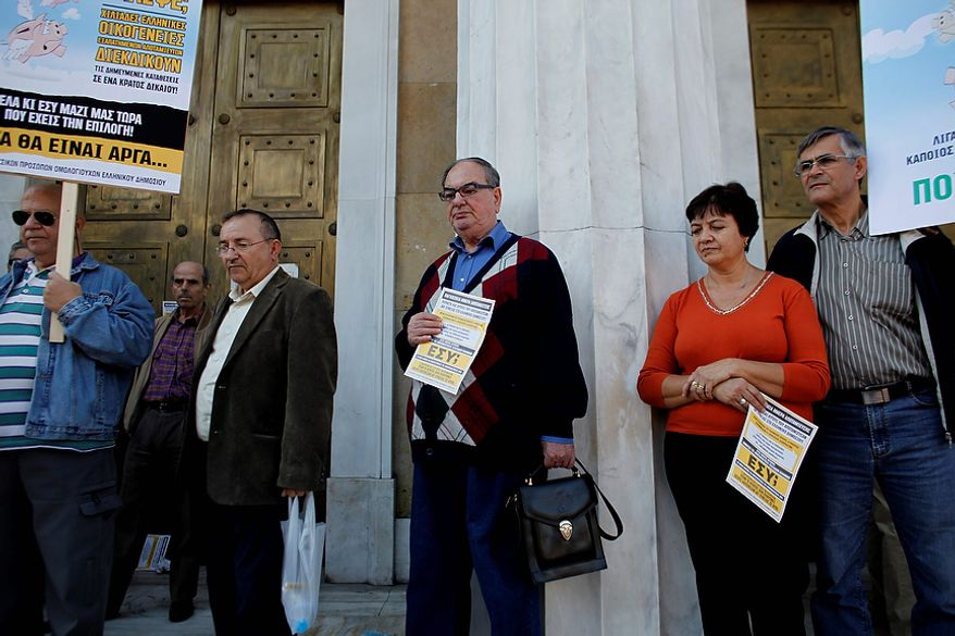 Greek bond holders stand at the entrance of Greece's central bank during a protest, in Athens Wednesday, Oct. 31 2012. Greece's two main labor unions covering civil servants and the private sector have called a 48-hour strike to protest austerity measures due to be voted on next week. The strike call came as the finance minister submitted an amended 2013 budget that raised the country's debt and deficit forecasts for next year. (AP Photo/Kostas Tsironis)