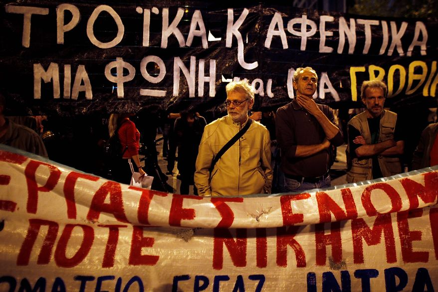 """Protesters stand in front of a banner reading """"Workers United never Defeated"""" during an anti-austerity protest by Greek labor unions in Athens, on Wednesday Oct. 31 2012. Greece's government on Wednesday outlined the new austerity measures it intends to take over the next two years, a series of painful spending cuts and tax hikes that its international bailout creditors are demanding in exchange for rescue loans. (AP Photo/Kostas Tsironis)"""