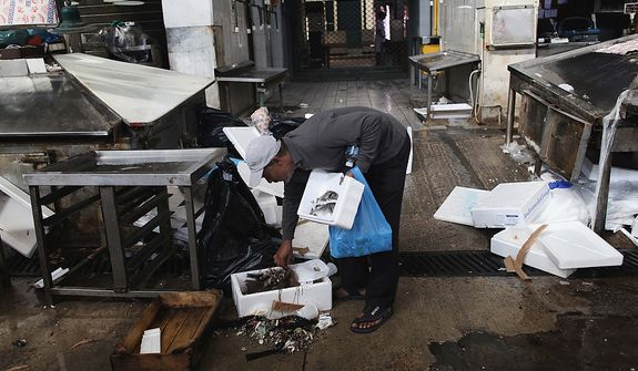 In this Monday, Sept. 24, 2012 file photo a man pick up fish inside the Athens' central fish market. To the casual visitor, all might appear well in Athens. But scratch the surface and you find a society in freefall, ripped apart by the most vicious financial crisis the country has seen in half a century. (AP Photo/Petros Giannakouris)