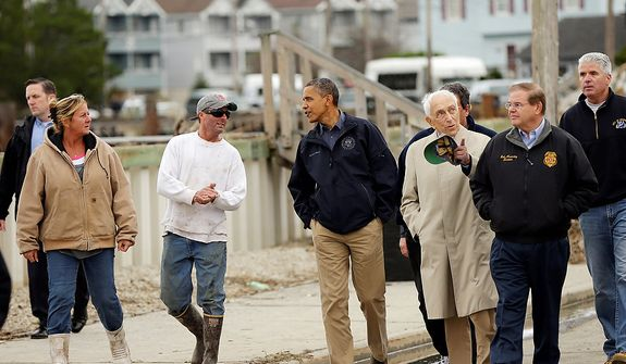 President Obama (center) talks with a resident as he tours a neighborhood affected by superstorm Sandy, on Wednesday, Oct. 31, 2012, in Brigantine, N.J. Walking with Mr. Obama are Sen. Frank Lautenberg and Sen. Bob Menendez (far right). (AP Photo/Pablo Martinez Monsivais)