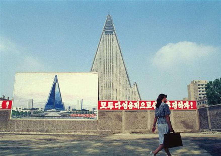 A North Korean woman walks past the construction site of the 105-story Ryugyong Hotel in Pyongyang, the North Korean capital, on Aug. 22, 1990. Work on the 3,000-room pyramidal building, begun almost a decade earlier, was expected to be completed in 1992 after financial problems. (AP Photo/Vincent Yu)