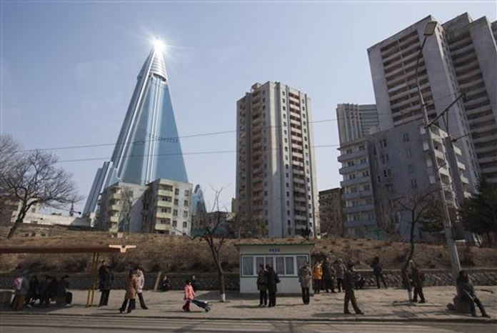 In this April 1, 2012, photo, the sun is reflected from the top of the 105-story Ryugyong Hotel, which remains under construction in Pyongyang, North Korea. International hotel operator Kempinski AG said on Thursday, Nov. 1, 2012, that it will manage the pyramid-shaped hotel, which is expected to open next year with shops, offices, ballrooms, restaurants and 150 rooms. (AP Photo/David Guttenfelder)