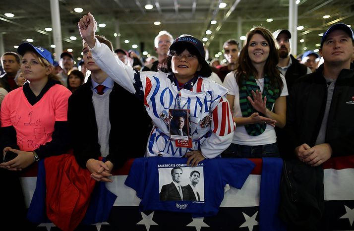 Supporter Annie Lin, from Salem, Va., center, wearing plastic Romney lawn signs, cheers Republican presidential candidate, former Massachusetts Gov. Mitt Romney while he speaks at a campaign event at Integrity Windows in Roanoke, Va., Thursday, Nov. 1, 2012. (AP Photo/Charles Dharapak)