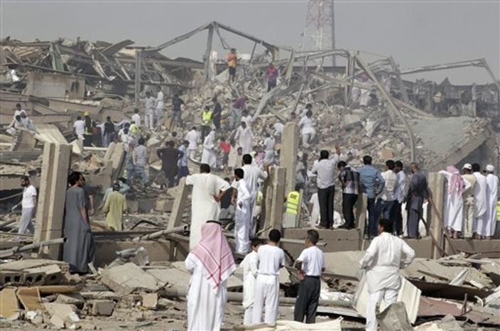 People walk among rubble at the site of a fuel truck explosion in Riyadh, Saudi Arabia, Thursday, Nov. 1, 2012. A fuel truck exploded after hitting portions of a bridge Thursday in the Saudi capital, Riyadh, engulfing buildings and cars in flames and killing dozens of people and injuring scores, witnesses and officials said. (AP Photo)