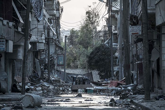 In this Tuesday, Oct. 30, 2012 photo, destroyed buildings are seen along a desolated street in the Bustan Al-Pasha district after several weeks of intense battles between rebel fighters and the Syrian army in Aleppo, Syria. (AP Photo/Narciso Contreras)