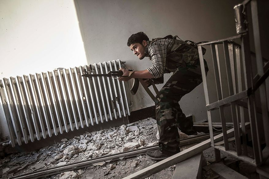 In this Tuesday, Oct. 30, 2012 photo, a rebel fighter belonging to the Liwa Al-Fatah takes cover as he aims at an enemy position from a school building during skirmishes with the Syrian army in the nearby Bustan Al-Pasha front line in Aleppo, Syria. (AP Photo/Narciso Contreras)