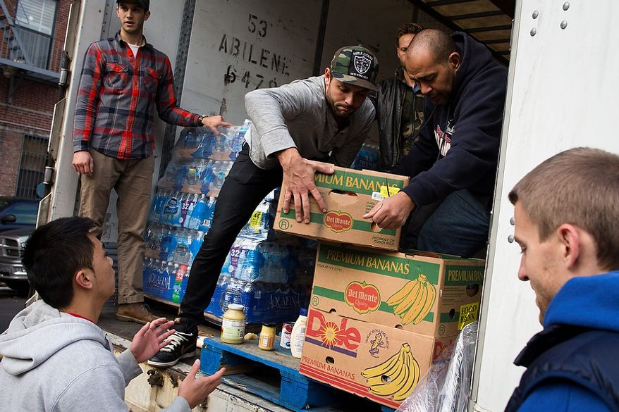 Volunteers help unload food from a truck for distribution to the residents of the Lower East Side who remain without power due to Superstorm Sandy, Friday, Nov. 2, 2012, in New York.  In Manhattan, where 226,000 buildings, homes and business remain without power, Consolidated Edison says they should have service restored by Saturday.  (AP Photo/ John Minchillo)
