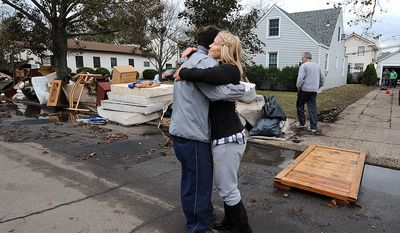 Beth Skudin, right, hugs a neighbor outside her home that was flooded by Superstorm Sandy, Thursday, Nov 1, 2012, in Long Beach, N.Y.  Skudin was rescued by jetski from the window of her home on the night of the storm. Three days after Sandy slammed the mid-Atlantic and the Northeast, New York and New Jersey struggled to get back on their feet, the U.S. death toll climbed to more than 80, and more than 4.6 million homes and businesses were still without power.  (AP Photo/Kathy Kmonicek)