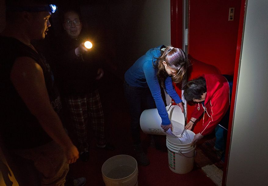 Grace Chow, 22, of New York, pours water from one bucket to another  for a resident on the twentieth floor at Confucius Plaza in the Chinatown neighborhood of New York, Thursday, Nov. 1, 2012. In the wake of Superstorm Sandy, power outages have also meant loss of water for some buildings. Chow and Matthew Hom, 26, also of New York, are volunteering for the New York United Dragon and Lion Dance group. (AP Photo/Craig Ruttle)