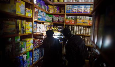 A shopkeeper assists a customer to buy dog food with a flashlight in a darkened Sheen Brothers corner store that remains without power due to Superstorm Sandy, Friday, Nov. 2, 2012, in New York. (AP Photo/ John Minchillo)