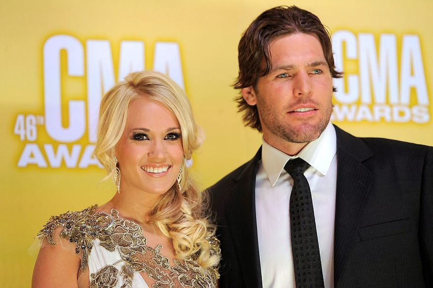 Carrie Underwood, left, and her husband Mike Fisher arrive at the 46th Annual Country Music Awards at the Bridgestone Arena on Thursday, Nov. 1, 2012, in Nashville, Tenn. (Photo by Chris Pizzello/Invision/AP)