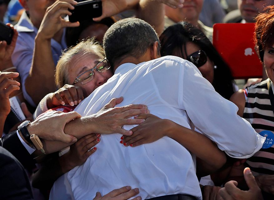 President Barack Obama is embraced by supporters during a campaign event at Cheyenne Sports Complex in Las Vegas, Thursday, Nov. 1, 2012. (AP Photo/Pablo Martinez Monsivais)