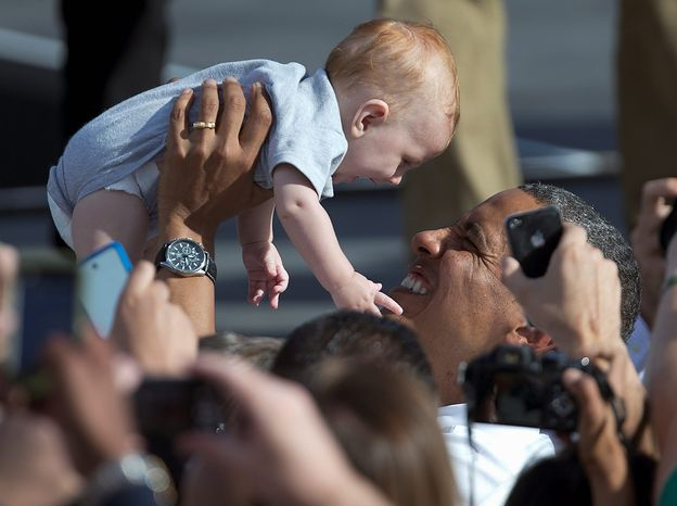President Barack Obama lifts a baby as he greets people in the audience after speaking at a campaign event, Thursday, Nov. 1, 2012, at the Cheyenne Sports Complex in Las Vegas, before heading to Denver. (AP Photo/Carolyn Kaster)
